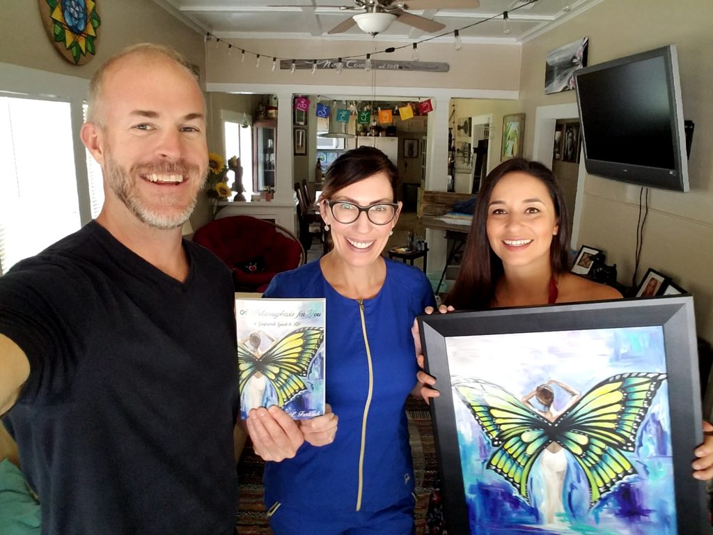 "Sean Donovan and Amy Frederick pose with a copy of the book ""A Metamorphosis for You"". Thays Franca holds the framed original painting used for the cover art."