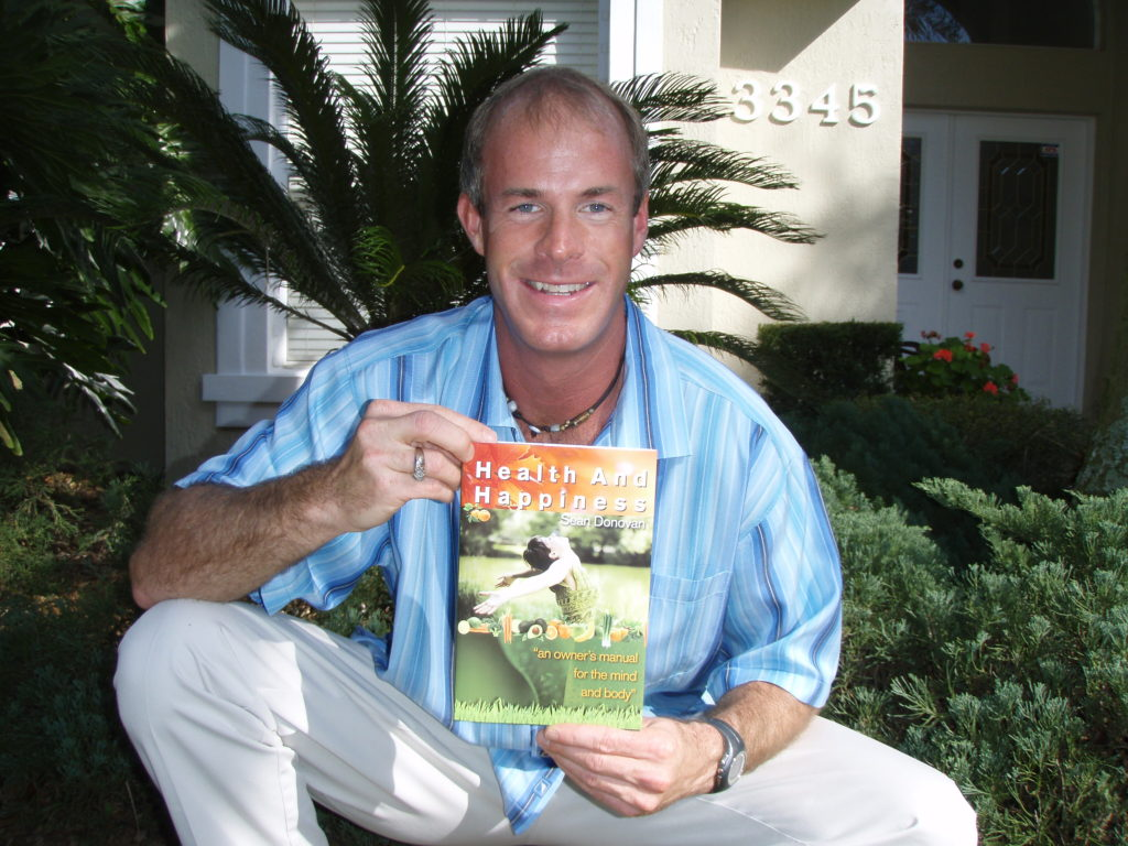 "Sean Donovan holding the first copy of his first book, ""Health and Happiness: an owner's manual for the mind and body"""
