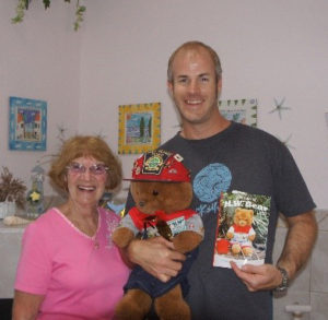 "Elaine Brayton, H.W. Bear, and Sean Donovan pose with a copy of ""The Tales of H.W. Bear"""