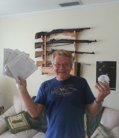 "Ken Kinsler posing with his writing and a copy of his book, ""Think Snow"""