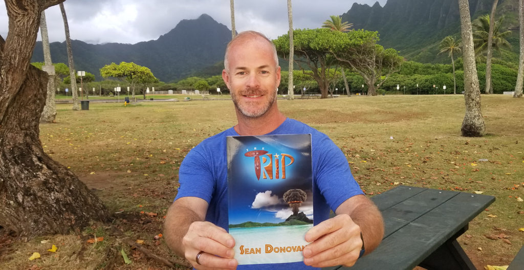 "Sean, posing with a copy of his first novel, ""The Trip""."